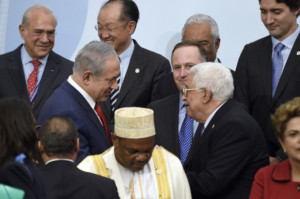 "Israeli Prime Minister Benjamin Netanyahu, center left, talks with Palestinian President Mahmoud Abbas, center right, as they wait to pose for a group photo as part of the COP21, the United Nations Climate Change Conference, in Le Bourget, outside Paris, Monday, Nov. 30, 2015. More than 150 world leaders are meeting under heightened security, for the 21st Session of the Conference of the Parties to the United Nations Framework Convention on Climate Change (COP21/CMP11), also known as ""Paris 2015"" from November 30 to December 11. (Martin Bureau/Pool Photo via AP)"