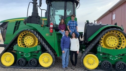 Entire family in front of tractor.