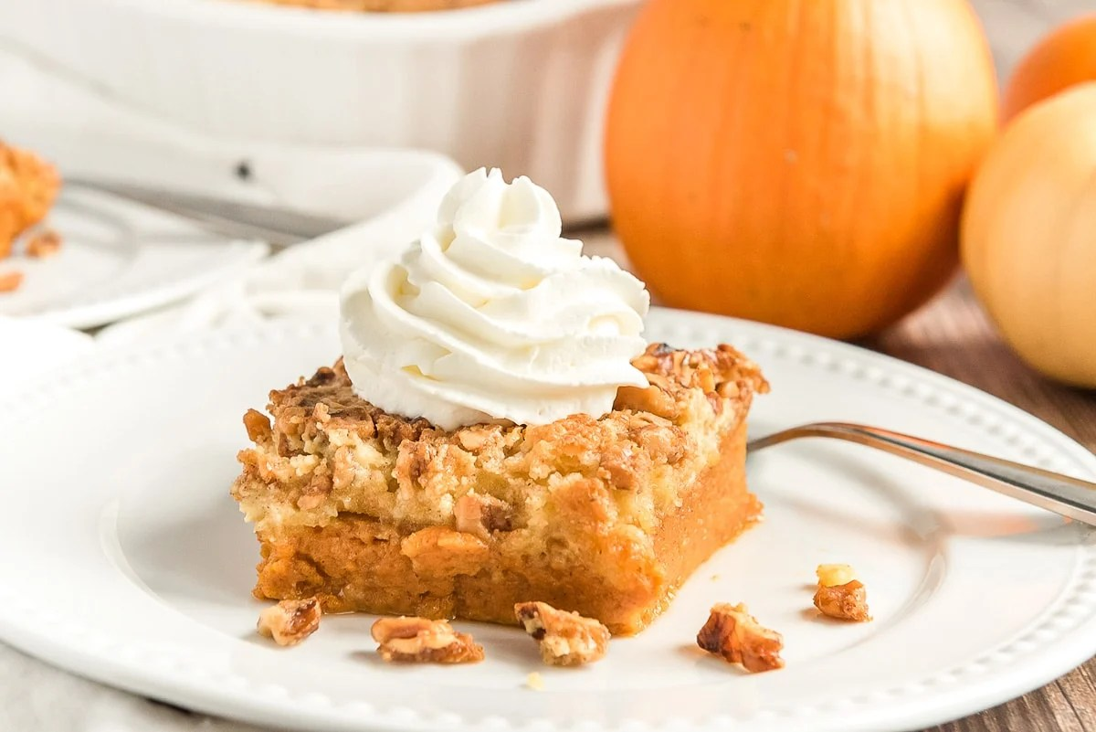 photo of a slice of pumpkin crunch cake on a white plate with pumpkins in the background.