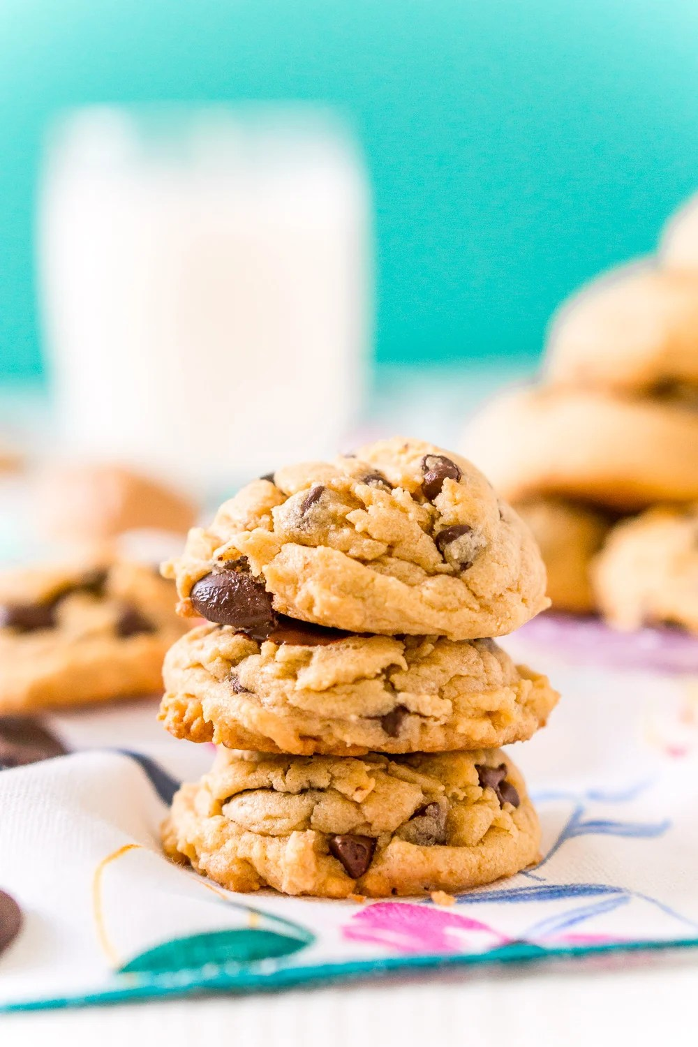 Three Peanut Butter Chocolate Chip Cookies stacked on top of each other with milk and more cookies in the background.