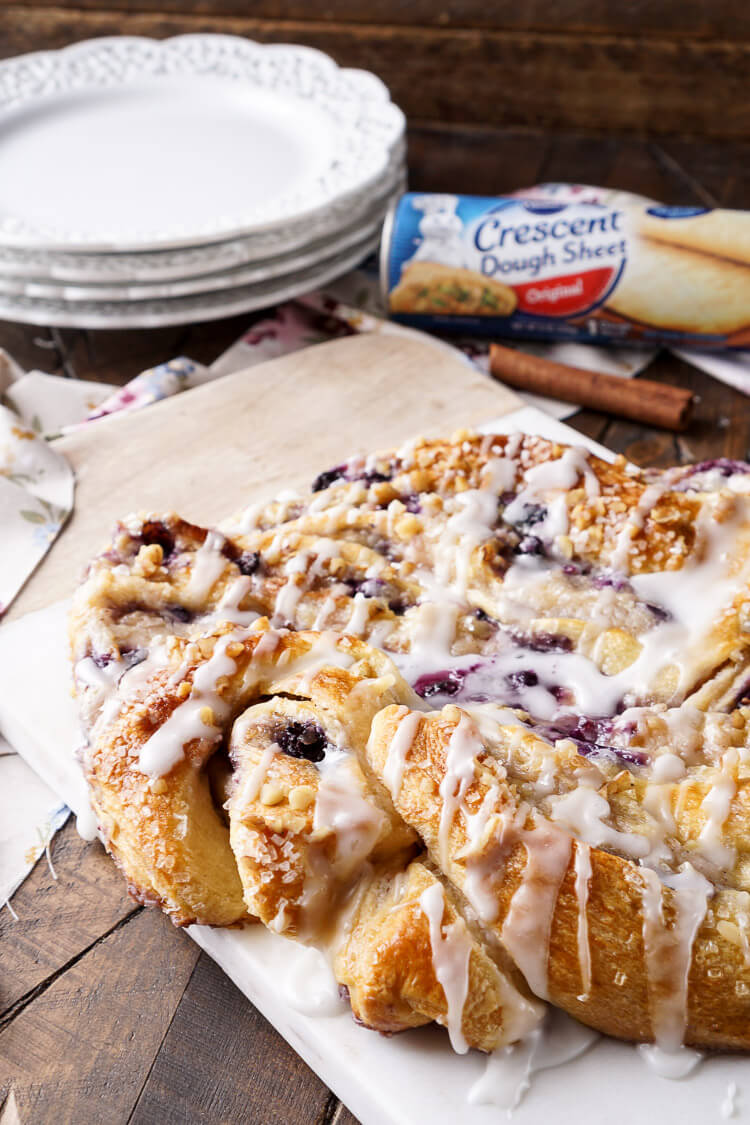 This Blueberry Spice Cream Cheese Breakfast Ring is the perfect addition to a holiday brunch. A simple and sweet filling is wrapped up in crescent dough and topped with chopped pecans and icing for a delicious morning pastry the whole family can enjoy!