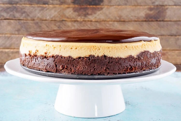 This Peanut Butter Chocolate Cheesecake recipe is a silky, peanut buttery dessert sandwiched between a chocolate graham cracker crust and a tempting chocolate ganache.
