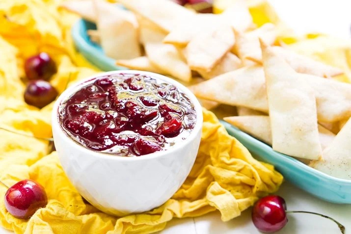 This Cherry Pie Dip is all the deliciousness of the classic pie but easier to make and perfect for parties! Fresh cherries are simmered into a thick and gooey dip served with cinnamon sugar pie chips!