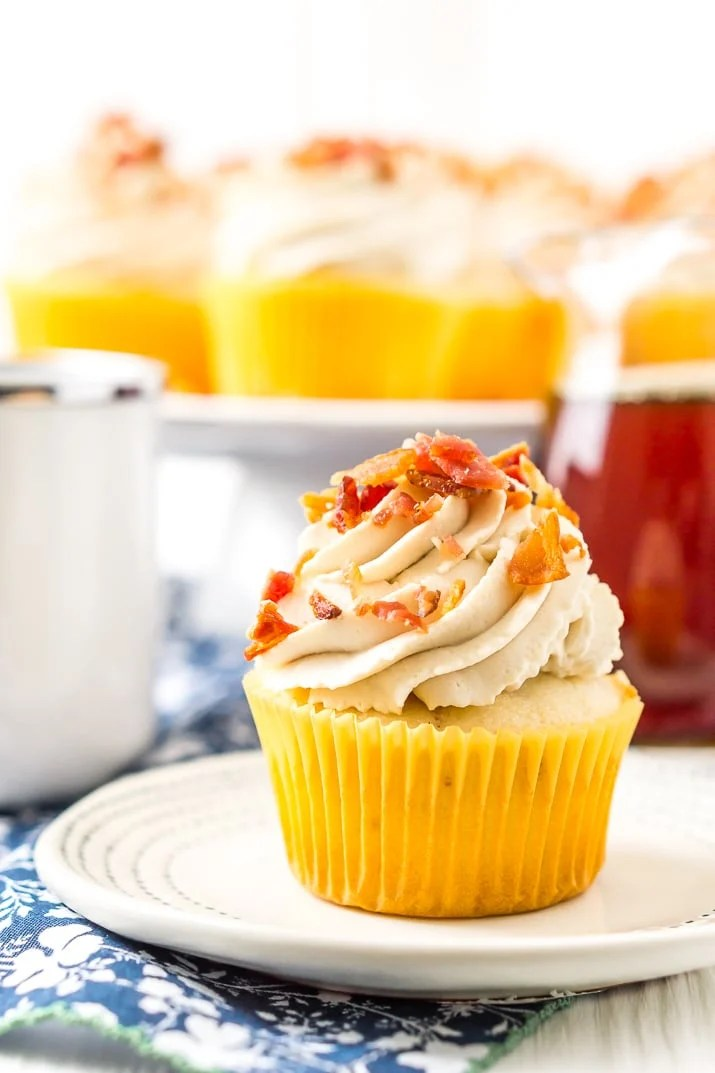 Maple Bacon Cupcakes on plate with cup of coffee and maple syrup