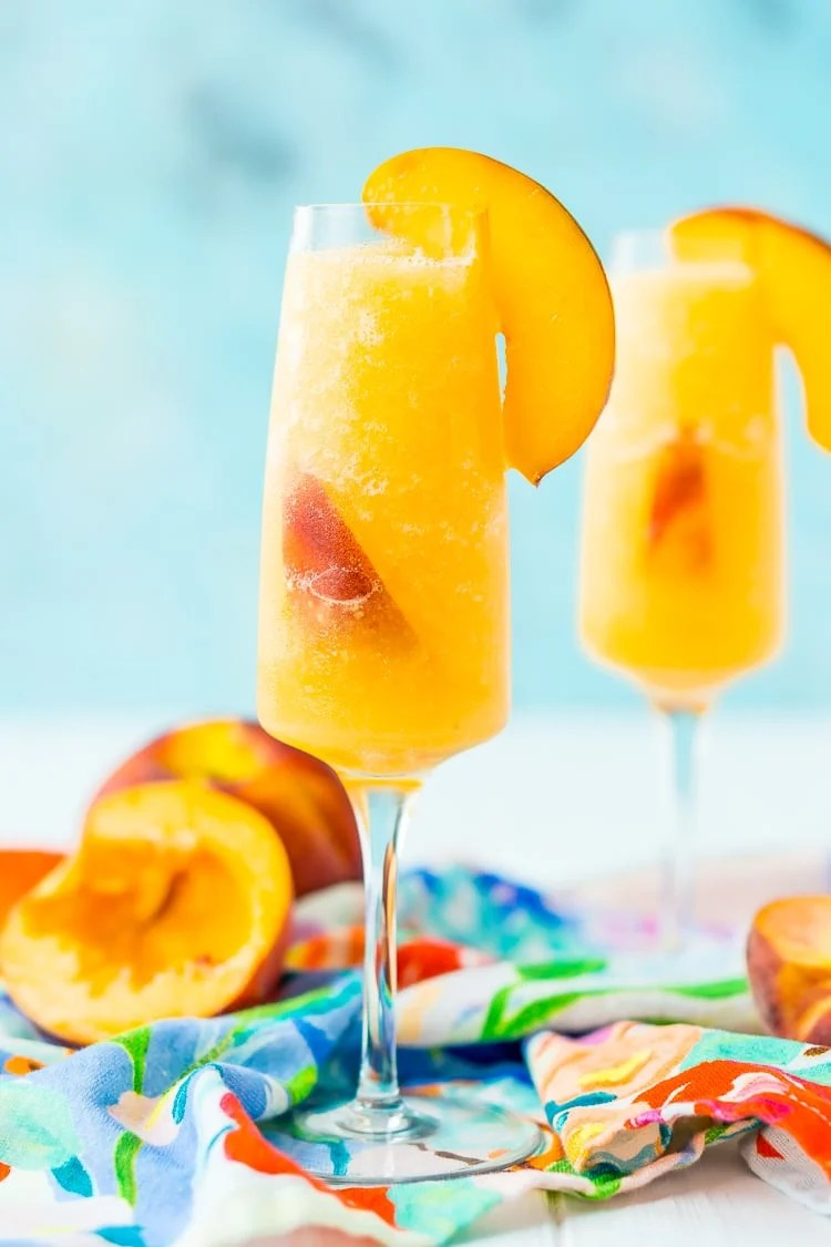 This Peach Bellini Slushies recipe is a frozen take on the classic brunch cocktail! Made in the blender with just 4 ingredients, this easy champagne cocktail is a refreshingly boozy beverage to enjoy all summer.