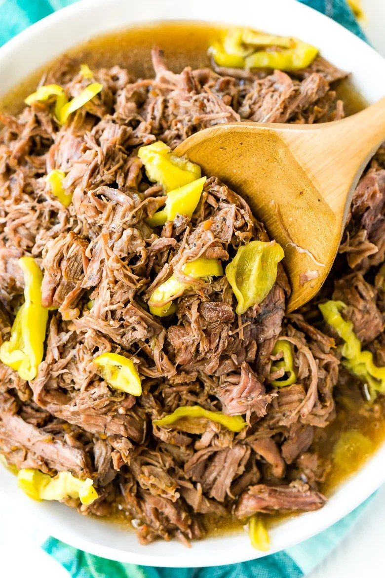 Italian Beef in white bowl with wooden spoon