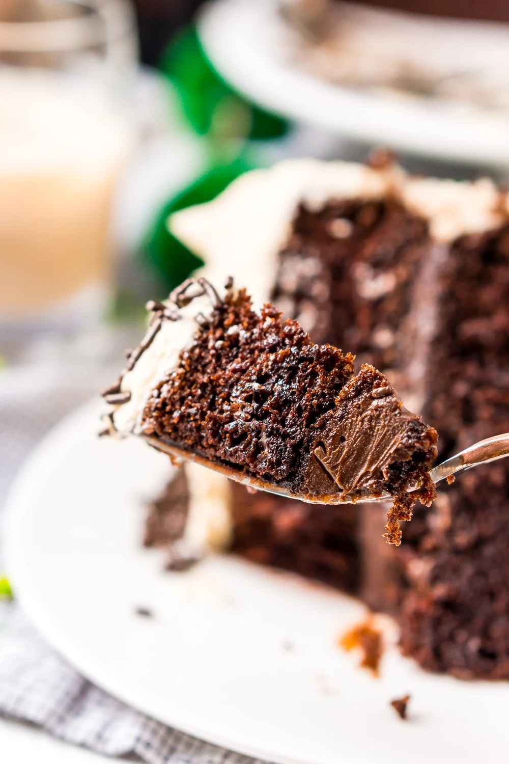 Bite of Chocolate Guinness Cake on a fork with slice of cake in the background.