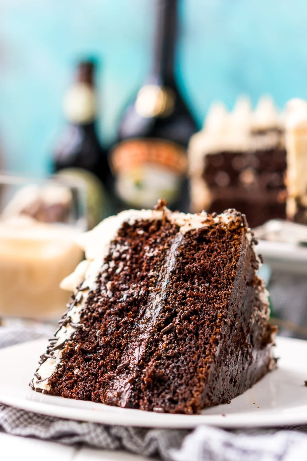 Slice of Chocolate Guinness Cake on a white plate with the rest of the cake, bottle of stout and irish cream in the background.