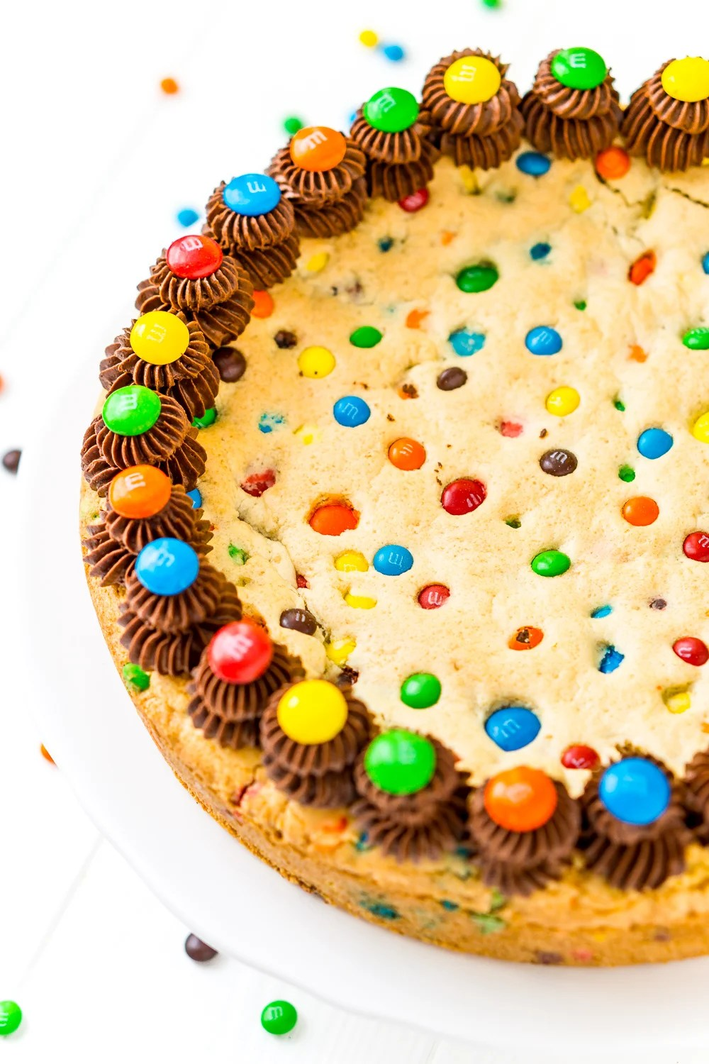 Close up of whole Cookie Cake with M&M's and chocolate frosting.