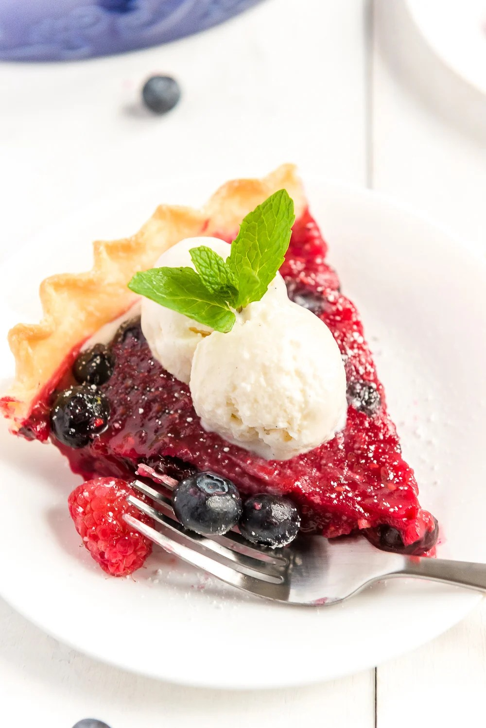 Angled photo of a slice of Mixed Berry Pie on a white plate with scoops of vanilla ice cream on top.