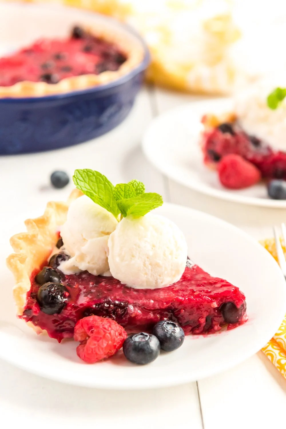 Slice of Mixed Berry Pie on a white plates with fresh berries, vanilla ice cream on top, and a sprig of mint.