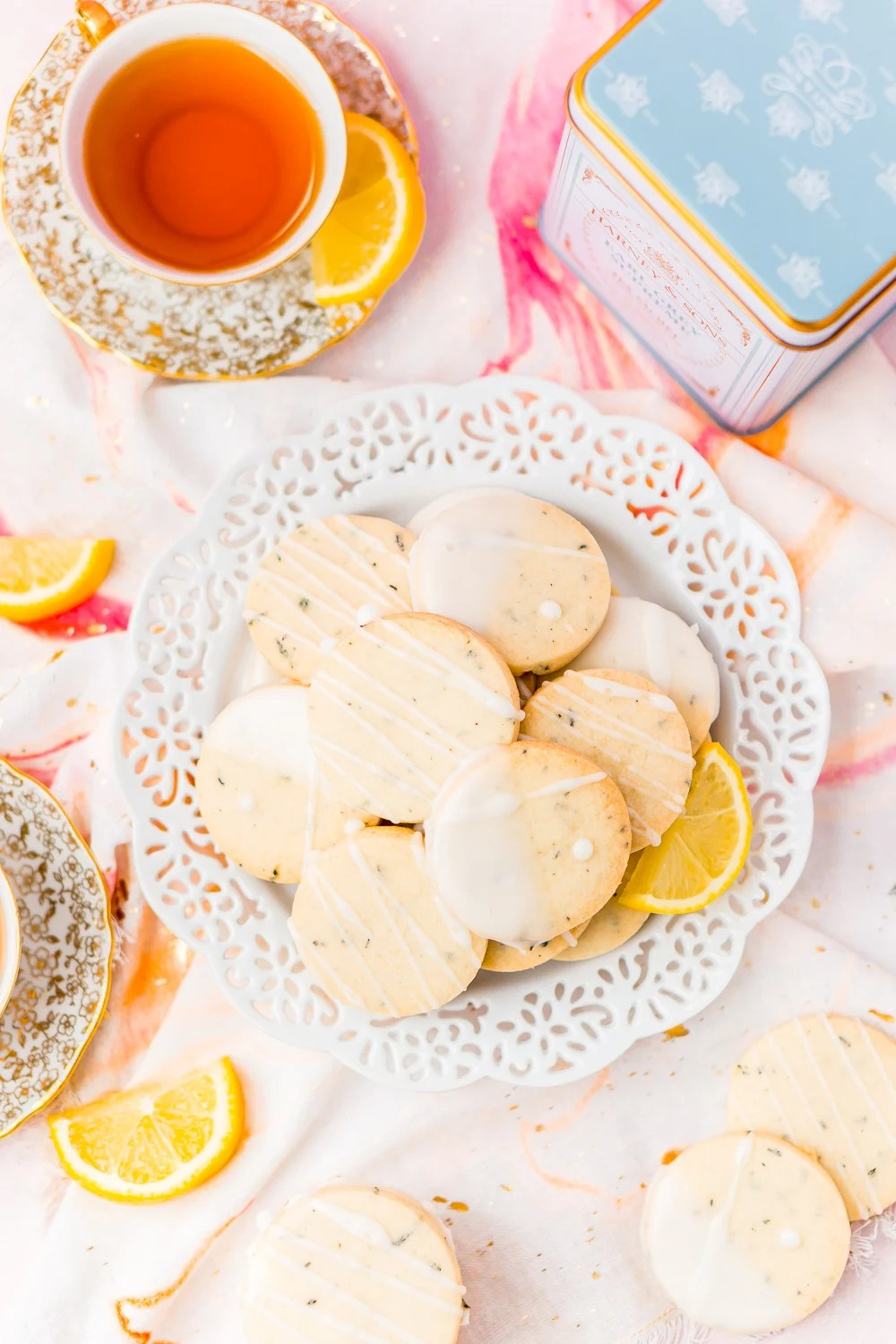 White plate filled with Earl Grey Shortbread Cookies with cups of tea and lemon slices.