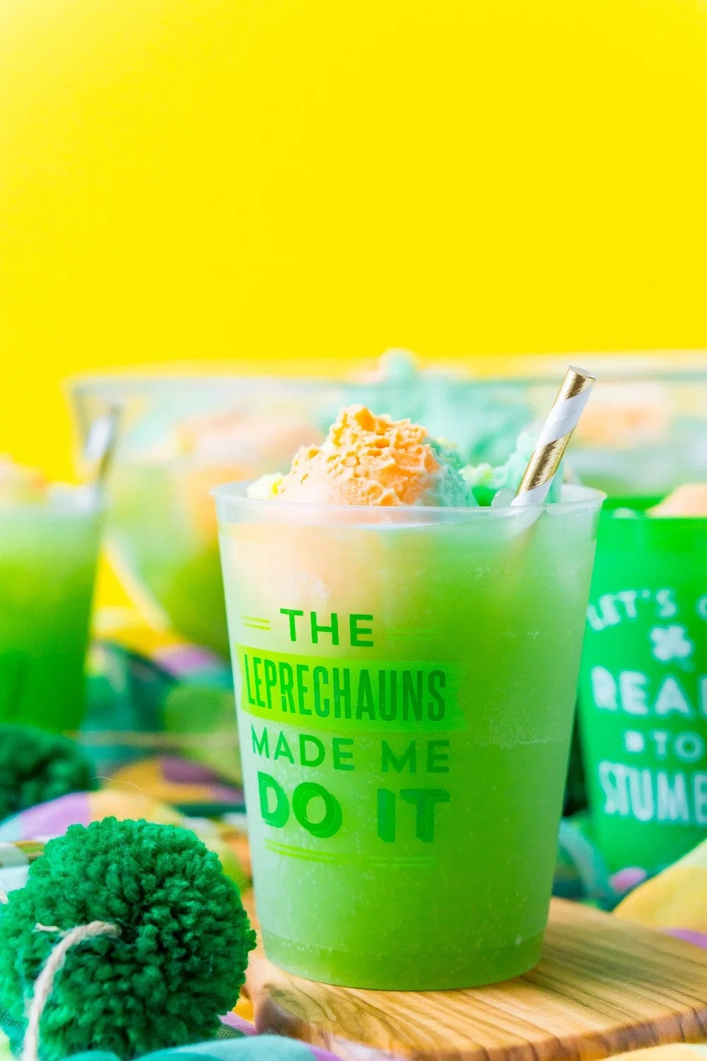 "Cup of St. Patrick's Day Punch that says "" The Leprechauns Made Me Do It"" on a wood board with a punch bowl and more cups in the background."