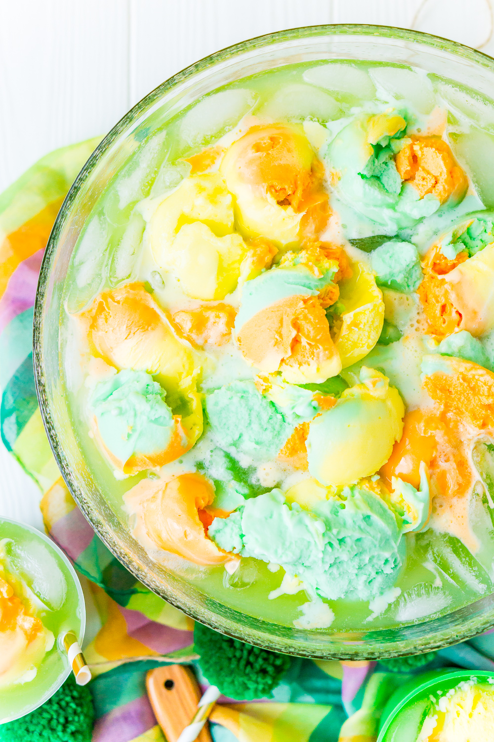 Overhead photo of a punch bowl filled with St. Patrick's Day Punch that's topped with rainbow sherbet.
