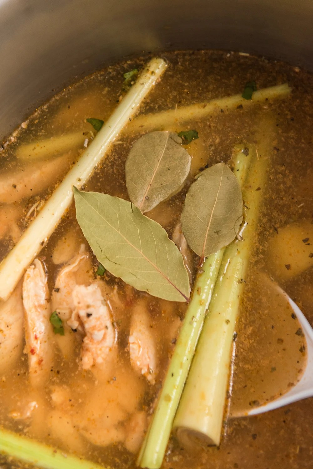 Ingredients for Chicken Coconut Soup (Tom Kha Gai) with broth in saucepan.