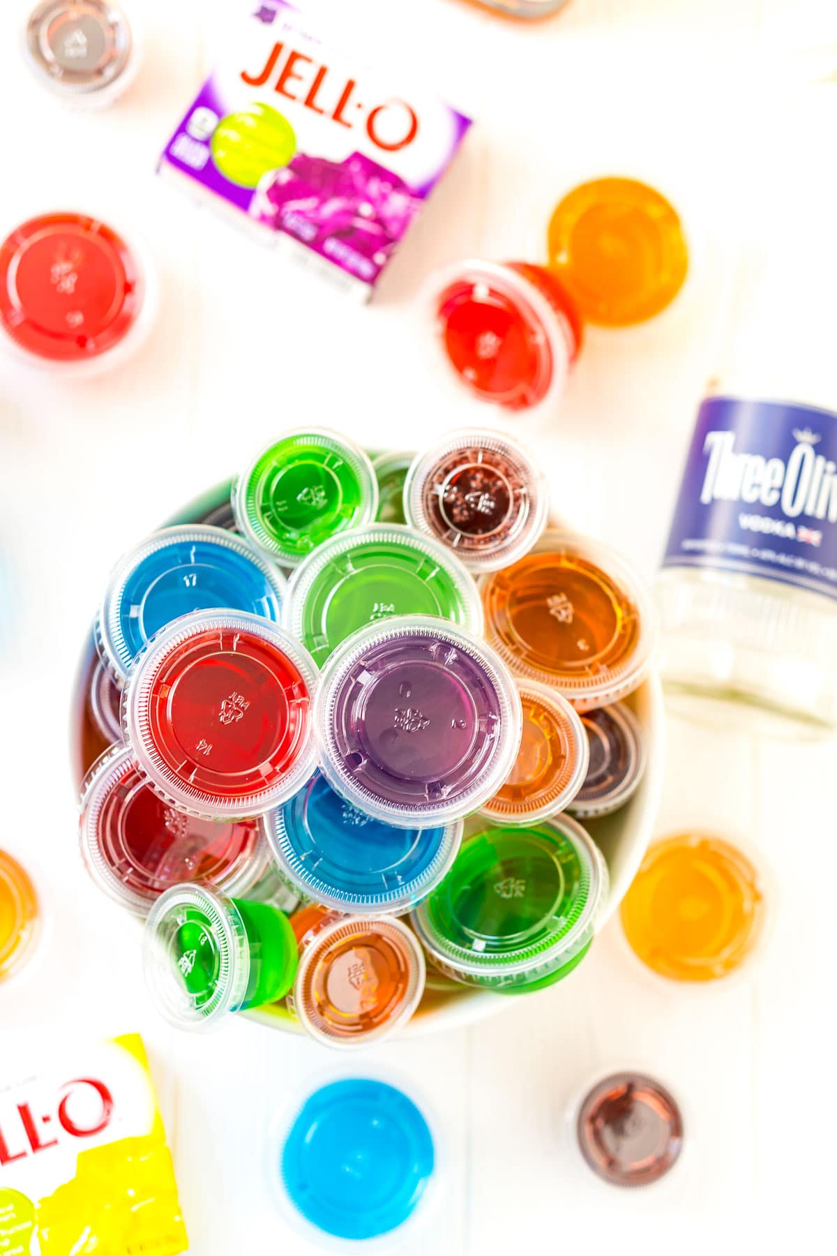 Bowl full of multi-colored jello shots with more jello shots, boxes of Jell-O, and a bottle of vodka around it.