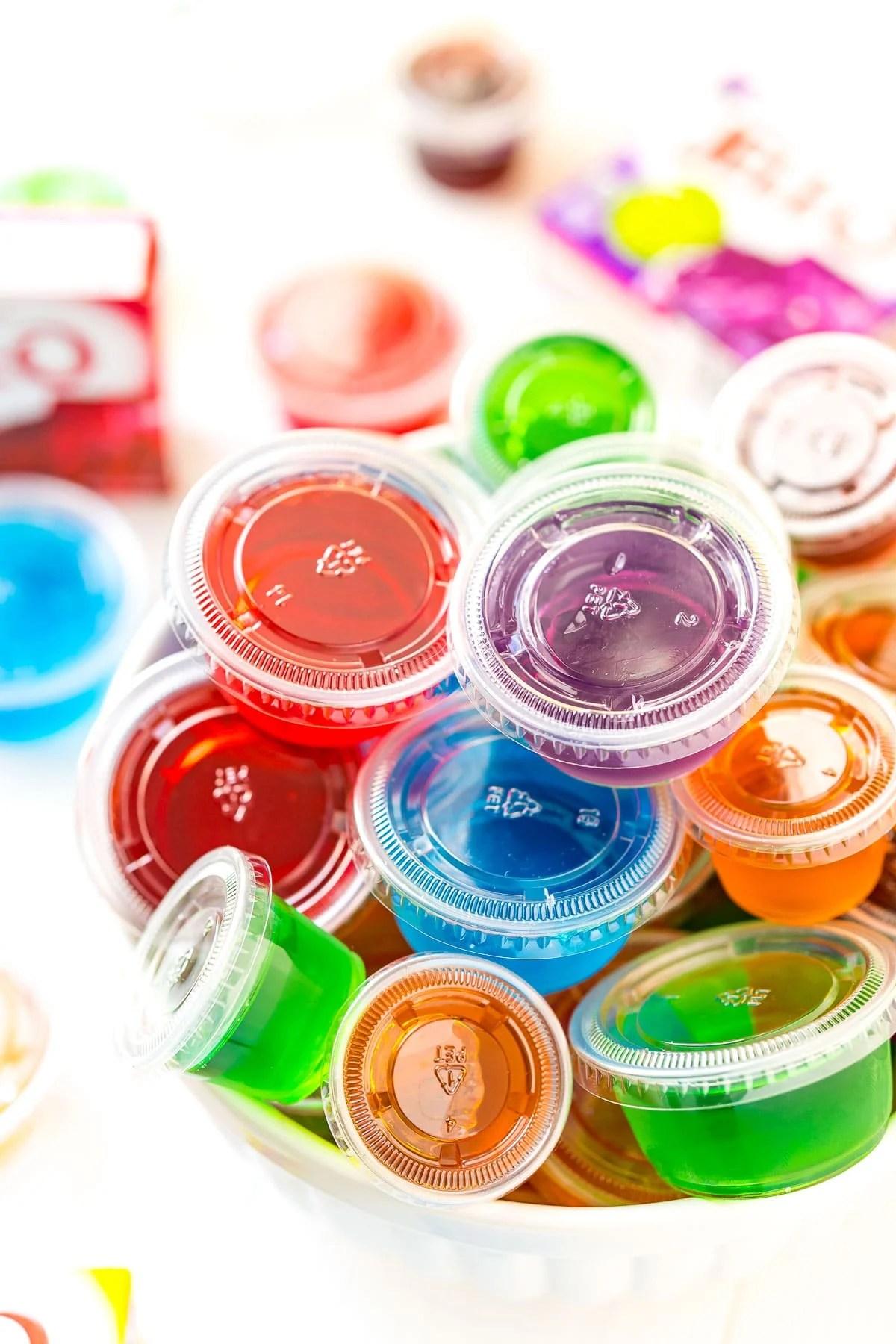 Multi colored jello shots in a white bowl.