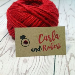 Photo Booth Wedding Tag with wedding ring around the hole punch. Names of the bride and groom in red writing