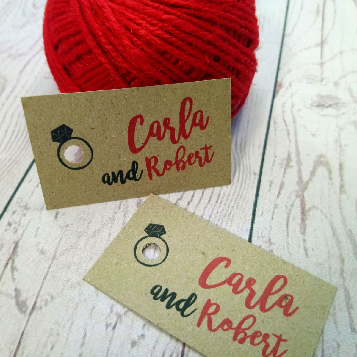 Photo Booth Wedding Tags with hole punch detaild of a wedding ring and bride and groom's names in red