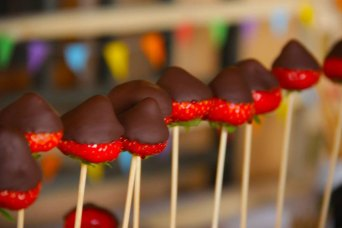Strawberries dipped in chocolate in a cocktail stick