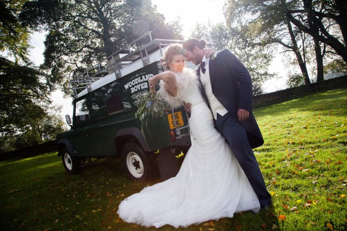 Bride and groom posing in front of Woodland Rover