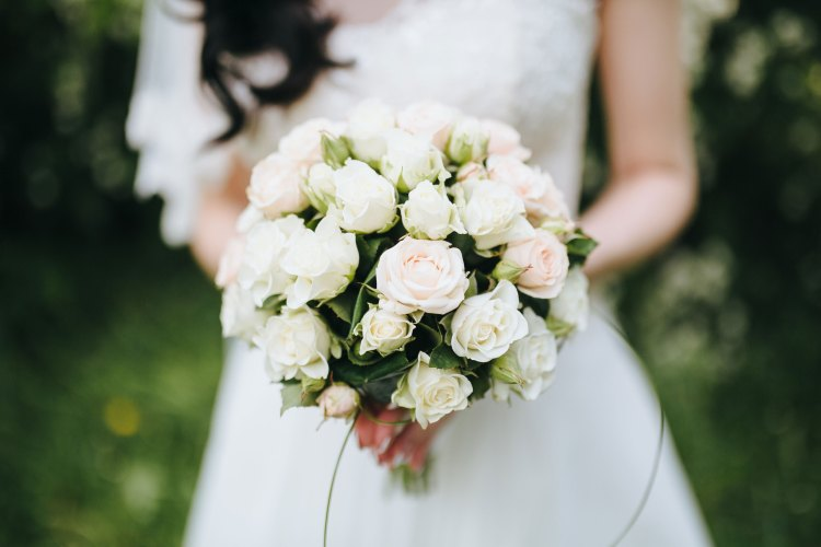 Bride posing with a classic white rose bouquet