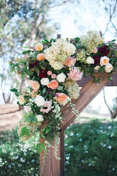 Detail Picture of flowers peach and burgundy of rustic wooden wedding arch