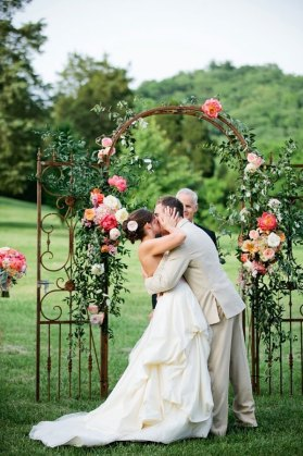 Bride and Groom kissing in front of a metal wedding arch