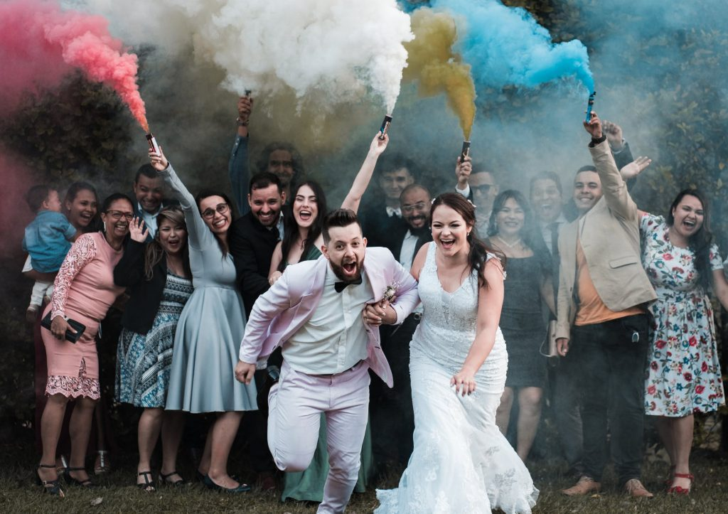 bride and groom running away from colour bombs with guests at the back