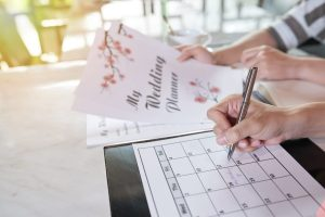 Young couple planning wedding day together and taking necessary notes in calendar while sitting at home, close-up shot