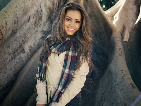 A smiling beautiful woman with a scarf on her neck