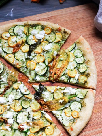 Pizza Pesto, Zucchini & Flowers-cut on a board