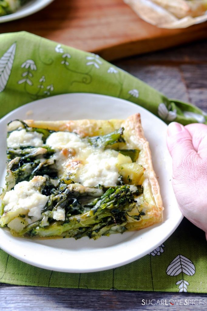 Broccolini and Potato Butter Pastry Tart-one piece in the dish with hand