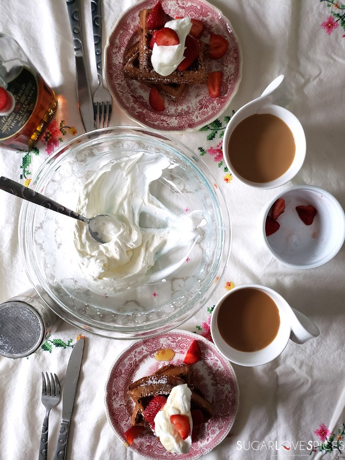 chocolate waffles with whipped cream and strawberries-table set for breakfast