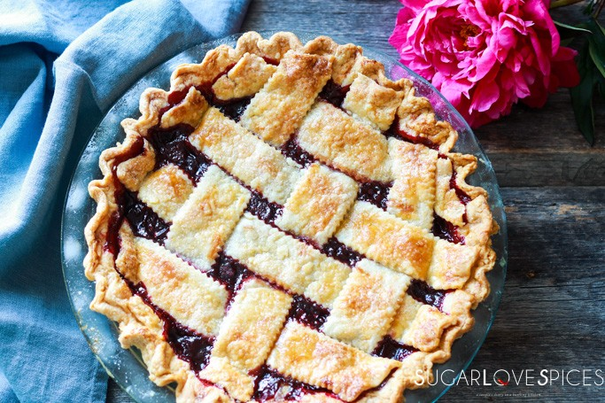 Homemade Cherry Berry Pie-baked pie on a wood surface with linen and peony