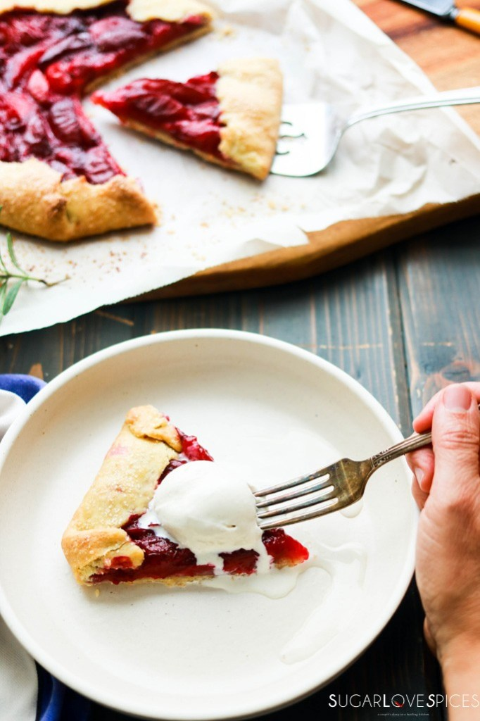 galette cut and a slice on a plate with ice cream on top, fork going in