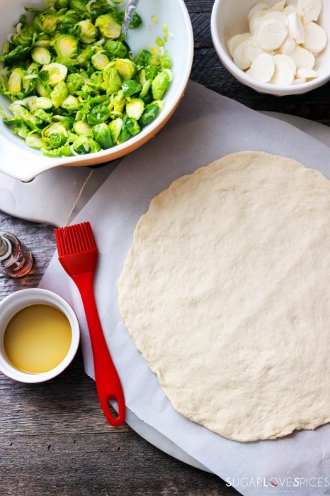 Shaved Brussels sprout pizza-stretched on parchment