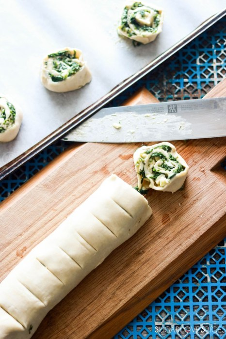 Spinach and Feta Pinwheels-cutting the roll on the board