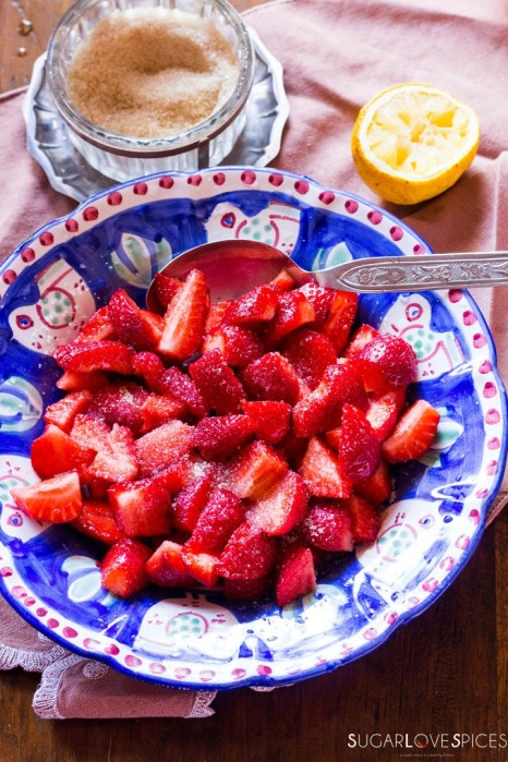 Strawberries with sugar and lemon-adding lemon