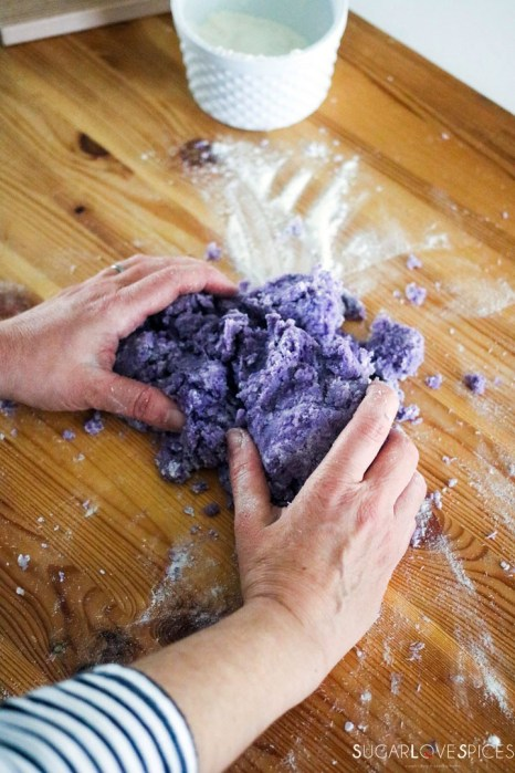 Homemade purple potato gnocchi-kneading gnocchi dough by hand on wood board
