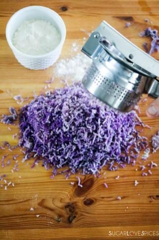 Homemade purple potato gnocchi-pressing potatoes through ricer on wood board