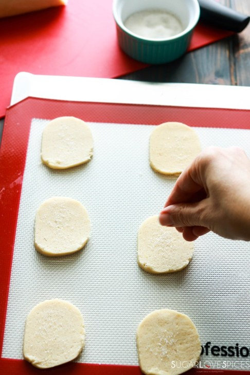 Slice and bake lemon crips-cookies on baking sheet-hand sprinkling sugar