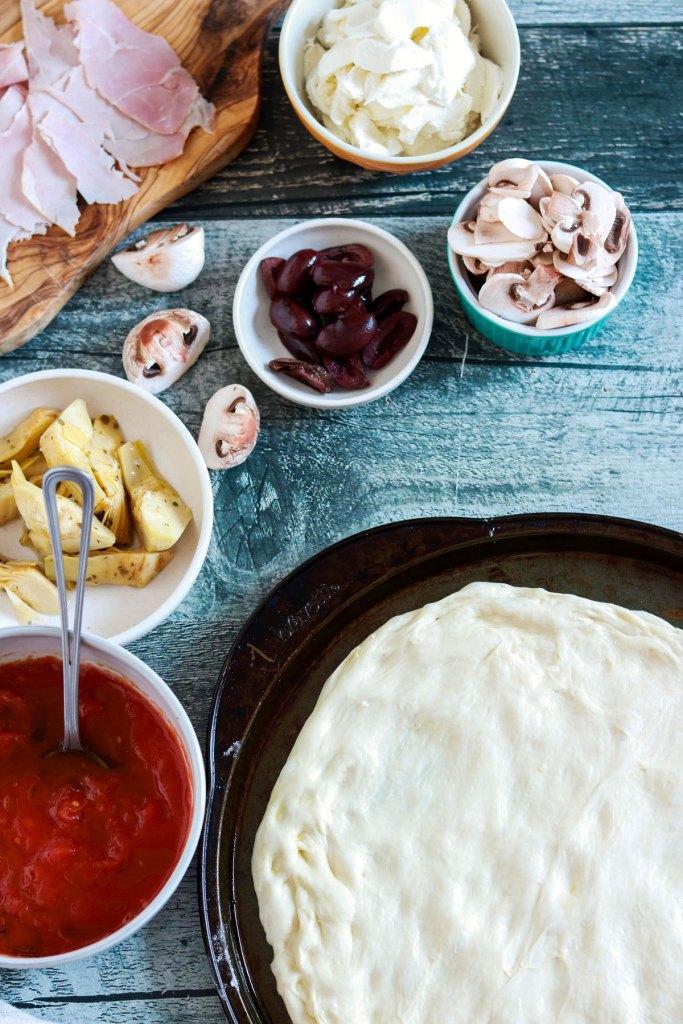 Capricciosa-pizza-pizza-spread-in-the-baking-sheet