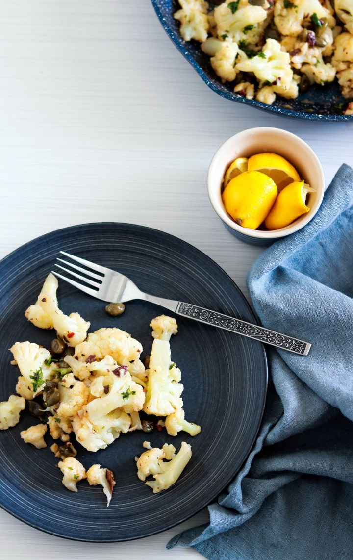 Quick and Delish Cauliflower with Lemon Caper Butter-some plated with fork-lemon on the side