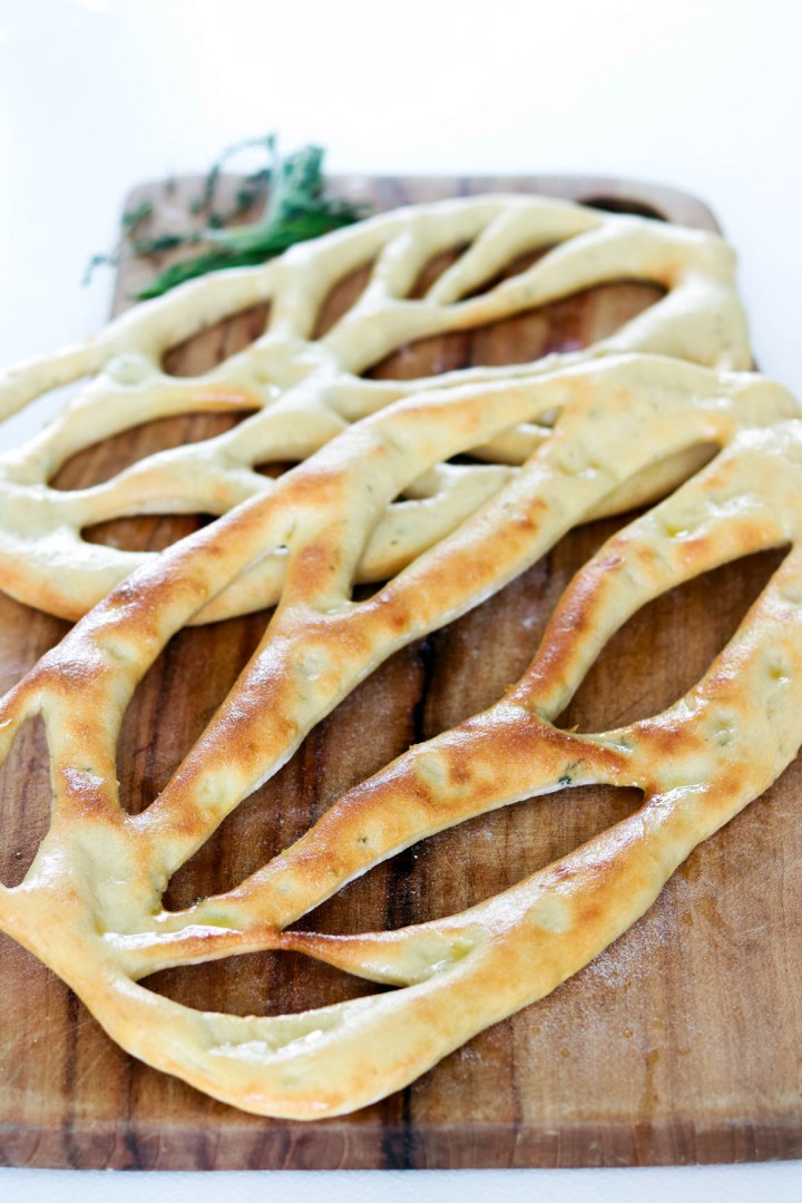 Fougasse, traditional Bread from Provence-bread on wood board-closeup-with herbs