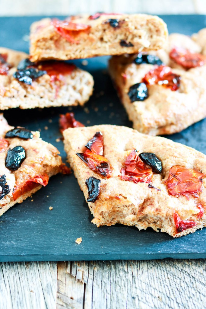 wholemeal spelt focaccia with olives and tomatoes-cut focaccia on a blackboard