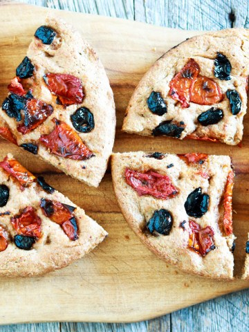 wholemeal spelt focaccia with olives and tomatoes-feature-cut focaccia on a wood board