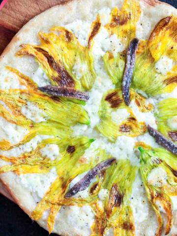 Zucchini blossom and anchovy Pizza (fiori di zucca e alici)-feature-pizza on a board-top view
