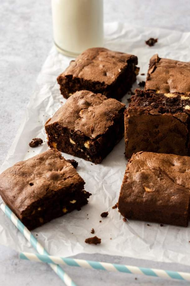 A batch of chocolate chip brownies on a sheet of baking paper with a bottle of milk in the background