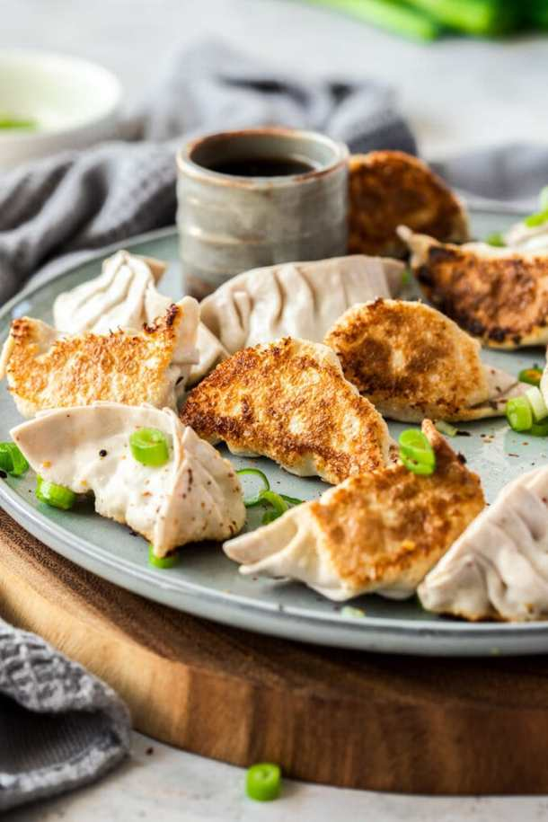 10 pork gyoza on a grey plate, that sits on a wooden platter. A small grey pot of sauce sits behind them